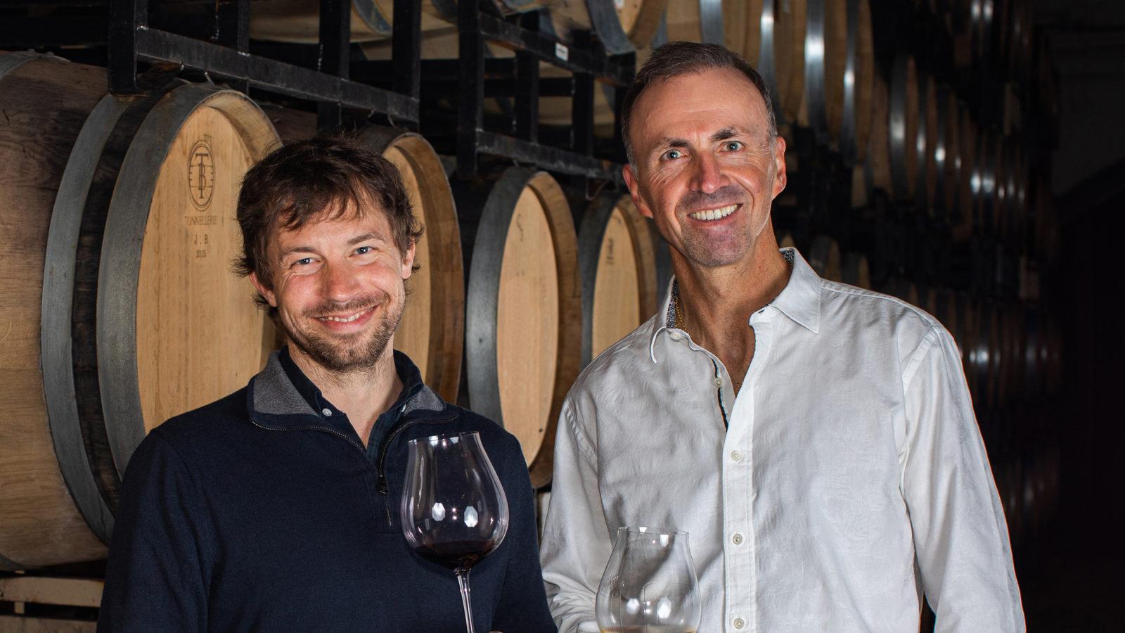winemaker and proprietor standing in front of wine barrels